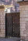 Smidesjärndörr av en trädgård- och murverkvägg i morgonen royaltyfria bilder