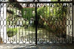 Smidesjärndörr framme av den fridsamma trädgården Arkivfoto