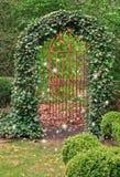 Smidesjärnport som täckas i murgröna, och feer som dansar i trädgård Arkivbilder