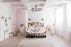 Smidesjärnsäng i det försiktiga ljusa rummet Vårblommagarnering fotografering för bildbyråer