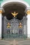 Smidesjärnskyddsgallerport med den imperialistiska dubblett-hövdade örnen och monogrammet på ingången av vinterslotten St Petersb Royaltyfria Bilder