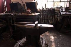 Smids` s workshop Werkende metaalhulpmiddelen in smidse Stock Foto