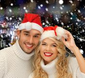 Smiiling couple in sweaters and santa helper hats Stock Image