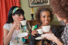 Smiilng Mature Women Having Tea. Group of three beautiful 1960s women having tea Royalty Free Stock Photography