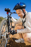 Smiing cyclist fixing his bike chain on country terrain Royalty Free Stock Image