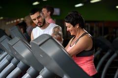 Smiing w średnim wieku kobieta i sprawność fizyczna trener w gym Obrazy Stock