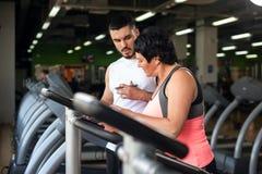 Smiing w średnim wieku kobieta i sprawność fizyczna trener w gym Obraz Royalty Free