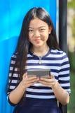 亚洲女孩和计算机压片与暴牙的smil的手中身分 免版税图库摄影