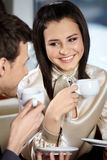 Smile. Man and woman in cafe drink coffee and smile, looking against each other Royalty Free Stock Image
