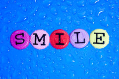 Smile. Color letter on blue background. Word smile Royalty Free Stock Photo