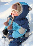 Smile. Baby laughing on snow during winter Royalty Free Stock Photography