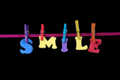 Smile. Letters forming the word smile put on a ribbon with colored washing pegs stock photo