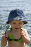 Smile. A very cute little girl with beautiful smile trying to wear her mom's sun glasses at the beach Royalty Free Stock Image