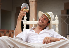 Smile. Smiling man sitting outdoor with glass of white wine stock photography
