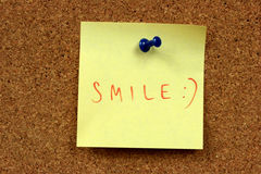 Smile. Yellow small sticky note on an office cork bulletin board. Happy message: smile and emoticon Royalty Free Stock Image