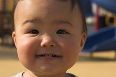 Smile. Asian baby smiling, with playground in the back stock photo