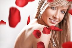 Smile. Beautiful portrait of blonde girl with smile and petals of roses royalty free stock photo