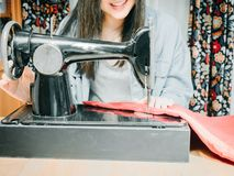 Smile from asian hipster girl 25s to 35s with blue jacket jean. During use black sewing machine with soft focus background Royalty Free Stock Photos