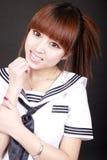 Smile Asian schoolgirl. Asian schoolgirl in traditional uniform on dark background Royalty Free Stock Photography