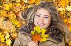 Smile in autumn leaves stock image