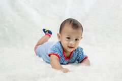 Smile baby boy is shooting in the studio. fashion image of baby and family. Lovely baby lie down on a soft white carpet. image for background, wallpaper, copy stock images