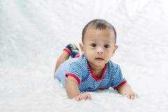 Smile baby boy is shooting in the studio. fashion image of baby and family. Lovely baby lie down on a soft white carpet. Image for background, wallpaper, copy royalty free stock photo