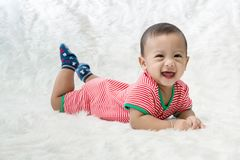 Smile baby boy is shooting in the studio. fashion image of baby and family. Lovely baby lie down on a soft white carpet. Image for background, wallpaper, copy royalty free stock image