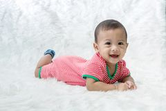 Smile baby boy is shooting in the studio. fashion image of baby and family. Lovely baby lie down on a soft white carpet. Image for background, wallpaper, copy royalty free stock photos