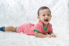 Smile baby boy is shooting in the studio. fashion image of baby and family. Lovely baby lie down on a soft white carpet. Image for background, wallpaper, copy stock photo