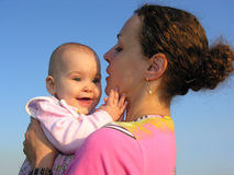 Smile baby on mother's hands. On blue sky stock image
