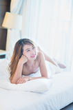 Smile Beautiful young woman in white bathrobe in bedroom at home Stock Images