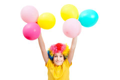Smile boy in clown wig holds hands up with balloons Royalty Free Stock Images