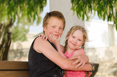 Smile, brother, smile!. Two happy hugging children: teen brother and little sister royalty free stock photos