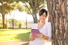 Smile brunette woman reading her ebook Royalty Free Stock Images
