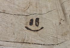 Smile burned into wood Stock Images