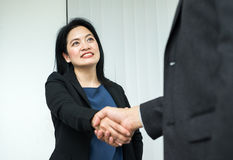 Smile Business woman and  business man shaking hand in office,Pa. Rtnership agreement concept Stock Photos