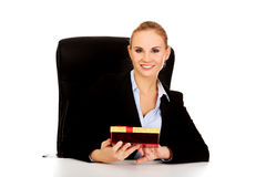 Smile business woman with gift box sitting behind the desk Royalty Free Stock Image