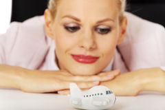 Smile business woman lying on the desk and looking for toy plane Stock Photo