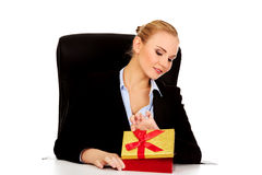Smile business woman opens a gift box behind the desk.  Royalty Free Stock Images