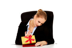 Smile business woman opens a gift box behind the desk.  Royalty Free Stock Photo