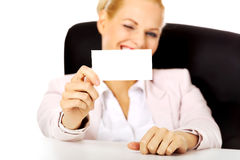 Smile business woman sitting behind the desk and holding empty buisiness card Royalty Free Stock Photography