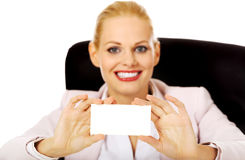 Smile business woman sitting behind the desk and holding empty buisiness card Stock Image