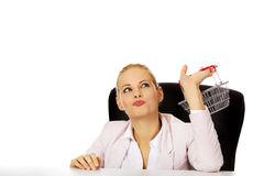 Smile business woman sitting behind the desk and holding small shopping basket Stock Photo