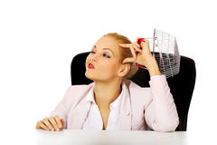 Smile business woman sitting behind the desk and holding small shopping basket Stock Images