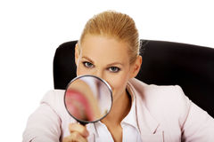 Smile business woman sitting behind the desk and looking into a magnifying glass Stock Photos