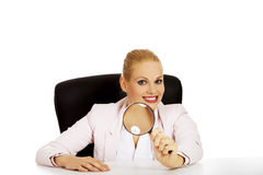 Smile business woman sitting behind the desk and looking into a magnifying glass.  Stock Image