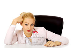 Smile business woman sitting behind the desk with small shopping basket Stock Photography
