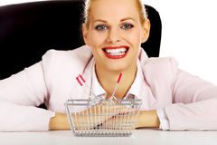 Smile business woman sitting behind the desk with small shopping basket Royalty Free Stock Image