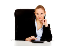 Smile business woman using calculator behind the desk Stock Images