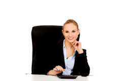 Smile business woman using calculator behind the desk Royalty Free Stock Images